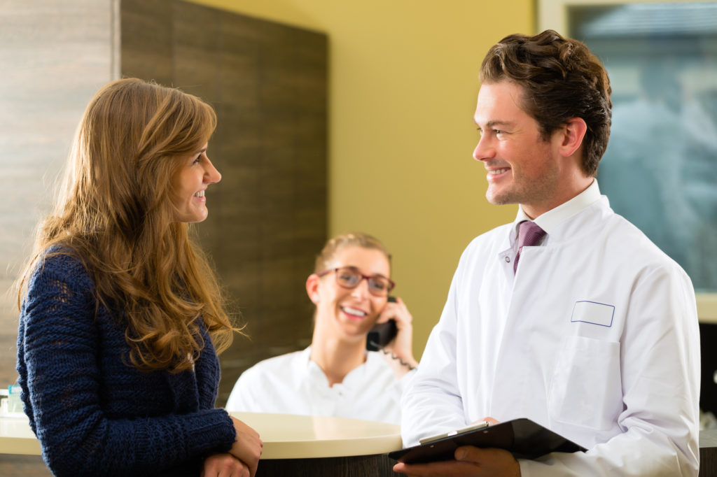 dentist and patient smiling at reception
